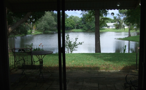 Photo of patio with small table and chair, gardens and lawn sloping down to a pond.